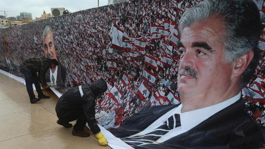 Workers set a giant poster of slain former Lebanese Prime Minister Rafik Hariri in preparation to mark the 10th anniversary of his assassination, at his grave in downtown Beirut, Lebanon, Wednesday, Feb. 11, 2015. An explosion that killed Hariri 10 years ago sent a tremor across the region and unleashed an uprising that briefly united the Lebanese and ejected Syrian troops from the country. But a decade later, and despite millions of dollars spent, justice remains elusive in a case that has been overshadowed by the current turmoil. (AP Photo/Hussein Malla)