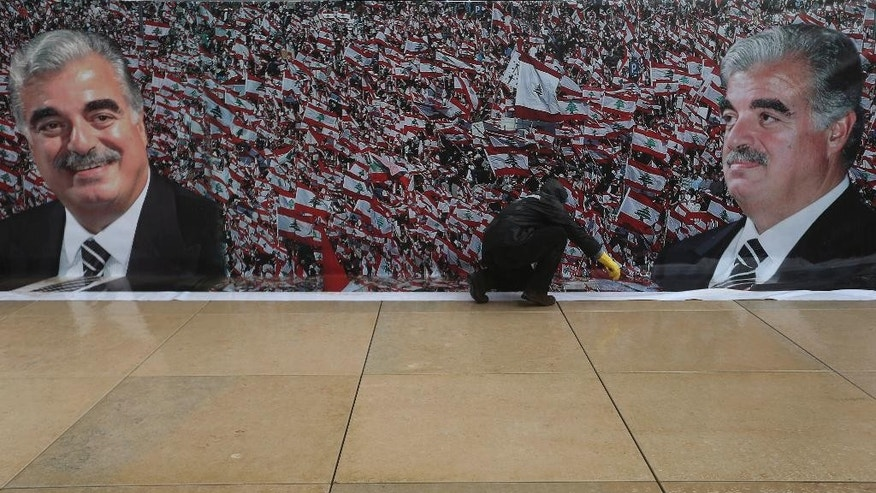 A worker sets a giant poster of slain former Lebanese Prime Minister Rafik Hariri in preparation to mark the 10th anniversary of his assassination, at his grave in downtown Beirut, Lebanon, Wednesday, Feb. 11, 2015. An explosion that killed Hariri 10 years ago sent a tremor across the region and unleashed an uprising that briefly united the Lebanese and ejected Syrian troops from the country. But a decade later, and despite millions of dollars spent, justice remains elusive in a case that has been overshadowed by the current turmoil. (AP Photo/Hussein Malla)