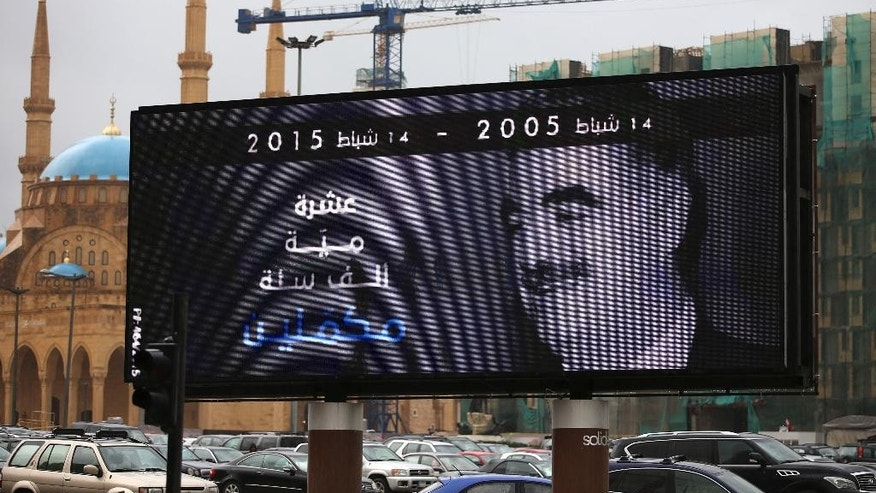 "A portrait of slain former Lebanese Prime Minister Rafik Hariri is seen on a digital billboard with Arabic words that read: ""Ten, hundred, one thousand years, we continue,"" in preparation to mark the 10th anniversary of his assassination, near his grave in downtown Beirut, Lebanon, Wednesday, Feb. 11, 2015. An explosion that killed Hariri 10 years ago sent a tremor across the region and unleashed an uprising that briefly united the Lebanese and ejected Syrian troops from the country. But a decade later, and despite millions of dollars spent, justice remains elusive in a case that has been overshadowed by the current turmoil. (AP Photo/Hussein Malla)"