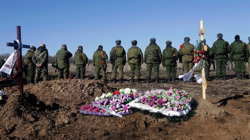 Russia-backed separatists pay respects to their comrade during a funeral at a cemetery in the east Ukrainian village of Mospino, near the city of Donetsk, Ukraine, on Thursday, Feb. 12, 2015. The militiaman was killed during recent fighting between Russia-backed separatists and government forces. Guns will fall silent, heavy weapons will pull back from the front, and Ukraine will trade a broad autonomy for the east to get back control of its Russian border by the end of this year under a peace deal hammered out Thursday after all-night negotiations between Russia, Ukraine, France and Germany. (AP Photo/Petr David Josek)