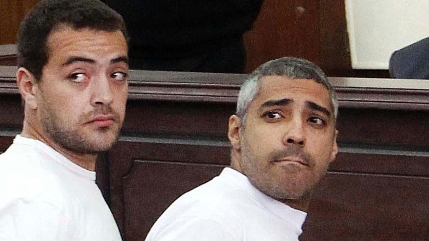 In this Monday, March 31, 2014 file photo, Al-Jazeera English producer Baher Mohamed, left, Canadian-Egyptian acting Cairo bureau chief Mohammed Fahmy, right, appear in court along with several other defendants during their trial on terror charges, in Cairo.