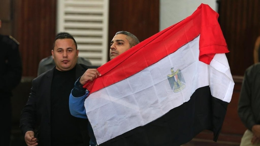 Mohamed Fahmy, a Canadian journalist of Al-Jazeera English, holds up an Egyptian flag after a retrial at a courthouse near Tora prison in Cairo, Egypt, Thursday, Feb. 12, 2015. An Egyptian judge ordered Fahmy and another Al-Jazeera English journalist, Baher Mohammed, released on bail Thursday as their retrial on terror-related charges continues. (AP Photo/Hassan Ammar)