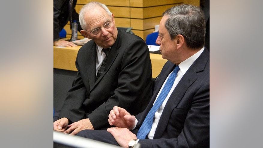 German Finance Minister Wolfgang Schaeuble, left, speaks with European Central Bank Governor Mario Draghi during a meeting of eurogroup finance ministers in Brussels on Wednesday, Feb. 11, 2015. Leading European officials downplayed expectations that a comprehensive debt deal with Greece is likely Wednesday at an emergency meeting in which Greece's finance minister is set to unveil a plan to loosen austerity's grip on his economy. (AP Photo/Virginia Mayo)