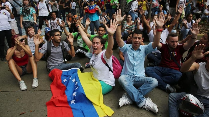 Anti-government demonstrator's chant slogans against the government during a protest in Caracas, Venezuela, Thursday, Feb. 12, 2015. Friends and foes of Venezuela's socialist government braved pouring rain to stage dueling marches on the anniversary of the protest movement that wracked the country last year. (AP Photo/Ariana Cubillos)