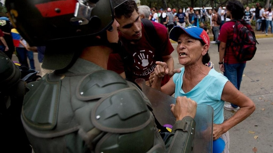 An opposition demonstrators argues with a Bolivarian National Guard officer during a protest to commemorating the anniversary of the protest movement that wracked the country last year, in Caracas, Venezuela, Thursday, Feb. 12, 2015. Friends and foes of Venezuela's socialist government braved pouring rain to stage dueling marches in the capital. (AP Photo/Fernando Llano)