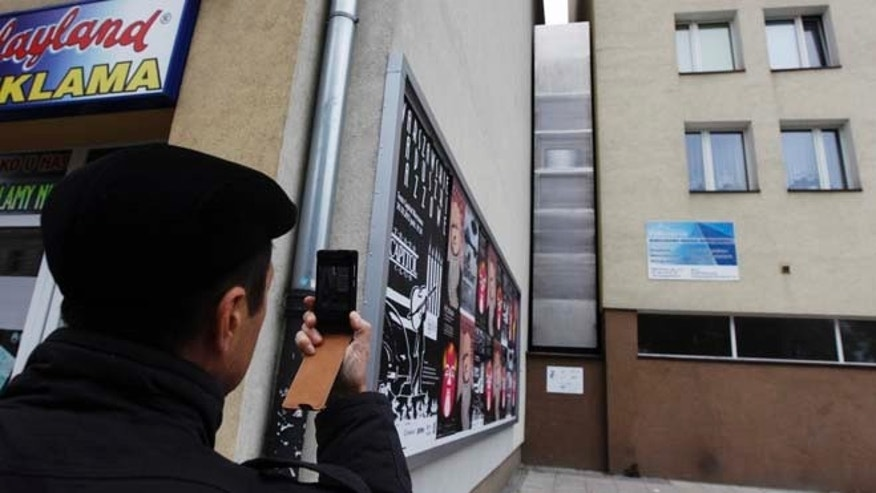 FILE 2012: A man takes a picture of the one of the world's narrowest buildings, built as an artistic installation wedged between two existing buildings in Warsaw.