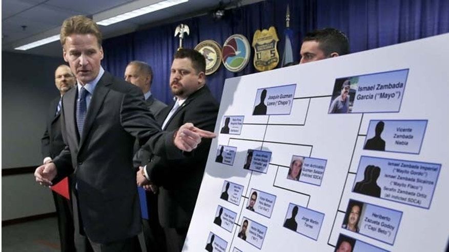 "U.S. Attorney Zachary T. Fardon makes reference to a chart of know Mexico-based Sinaloa Cartel members, during a news conference after twin brothers Pedro and Margarito Flores were sentenced to 14 years for their drug related activities in the cartel, Tuesday, Jan. 27, 2015, in Chicago. Fardon characterized the Flores brothers cooperation in bringing down the cartel as extraordinary. He says their reduced sentences should illustrate to criminals that, ""You can right some of what you did wrong, by helping the government."" (AP Photo/Charles Rex Arbogast)"