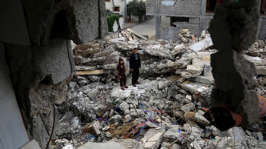 In this Wednesday, Nov. 26, 2014 photo, Mohammed Al-Bayoumi, 39, and his son Mahmoud stand on the rubble of their family home in the Nusseirat refugee camp in the central Gaza Strip. A July 31 Israeli airstrike killed 13 people from two families, including his son. The number of civilian deaths has been a key issue in the highly charged battle over the dominant narrative of last summer's 50-day war, the third and most destructive confrontation between Israel and Hamas since 2008. (AP Photo/Adel Hana)