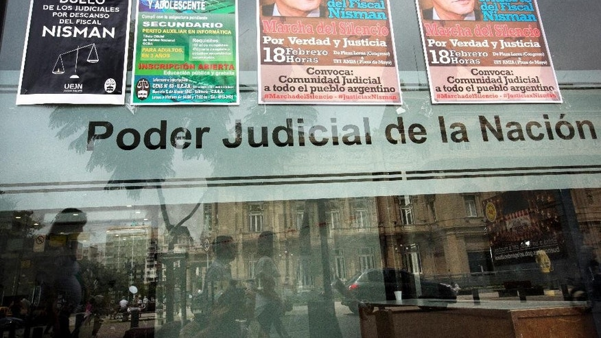 Posters announcing a march organized by federal prosecutors in demand for justice to commemorate the first month after the death of prosecutor Alberto Nisman, are seen on a window in Buenos Aires, Argentina,Tuesday, Feb. 10, 2015. Nisman's mysterious death came as he was presenting allegations that Argentine President Cristina Fernandez had conspired to protect Iranian officials implicated in the 1994 bombing of a Jewish community center in which 85 people died. Fernandez and Iran have denied the allegations.  (AP Photo/Rodrigo Abd)