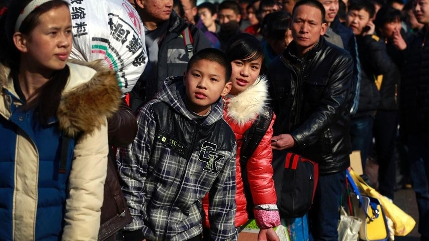 Chinese travelers queue up at the main entrance of the Beijing railway station in Beijing, Friday, Feb. 13, 2015. Millions of Chinese will be traveling to their hometowns to celebrate the Lunar New Year on Feb. 19 this year which marks the Year of the Sheep on the Chinese zodiac. (AP Photo/Andy Wong)