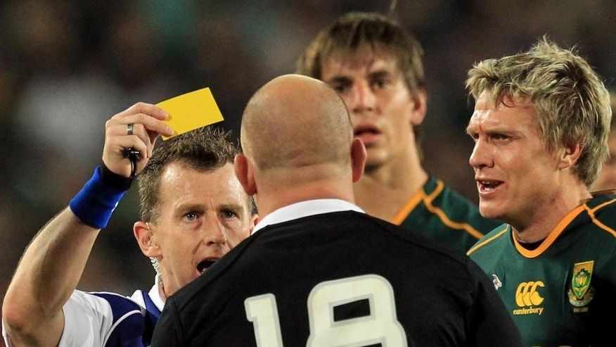 FILE - This Saturday, Oct. 5, 2013, file photo shows referee Nigel Owens of Wales, left, showing a yellow card to New Zealand's Ben Franks, foreground, as South Africa's captain Jean de Villiers, right, looks on during their Rugby Championship match at Ellis Park Stadium in Johannesburg, South Africa. For Nigel Owens, it is no real surprise that so few others in professional sports have followed his lead and come out as gay. Society is ready to accept gay footballers and rugby players, but the athletes themselves are not, the rugby referee extraordinaire says in an Associated Press interview. (AP Photo/Themba Hadebe, File)