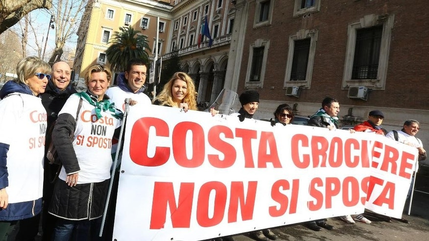"Protesters hold a banner reading in Italian ""Don't move, Costa"" in Genoa, Italy, Friday, Feb. 13, 2015. Costa Crociere's chief executive is facing a public relations battle over the company's future in Italy on the heels of the guilty verdict and 16-year sentence against former captain Francesco Schettino for deaths of 32 people in the 2012 shipwreck of the Costa Concordia. Costa's German CEO Michael Thamm met Friday with Italy's transport minister to offer assurances that the Italian cruise company owned by U.S. parent Carnival has no plans to move the headquarters out of Italy. Thamm was summoned to Rome after Costa announced it was moving four departments with 160 people from its Genoa headquarters to Hamburg, Germany.  Thamm said afterward that ""Italy remains a market with huge potential."" In Genoa, union members protested the announced transfers, saying they will weaken the company's Italian identity. (AP Photo/Luca Zennaro, Ansa)"