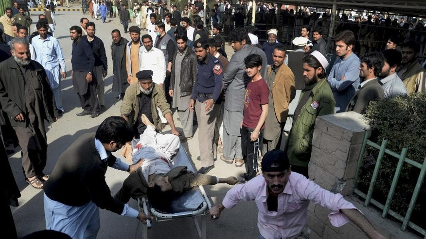 People rush an injured person to a hospital following an attack involving suicide bombers and gunmen at a Shiite mosque in Peshawar, Pakistan, Friday, Feb. 13, 2015. Militants stormed a Shiite mosque in northwestern Pakistan on Friday, killing many people in a wave of shooting and explosions before the siege ended, officials said. (AP Photo/Mohammad Sajjad)