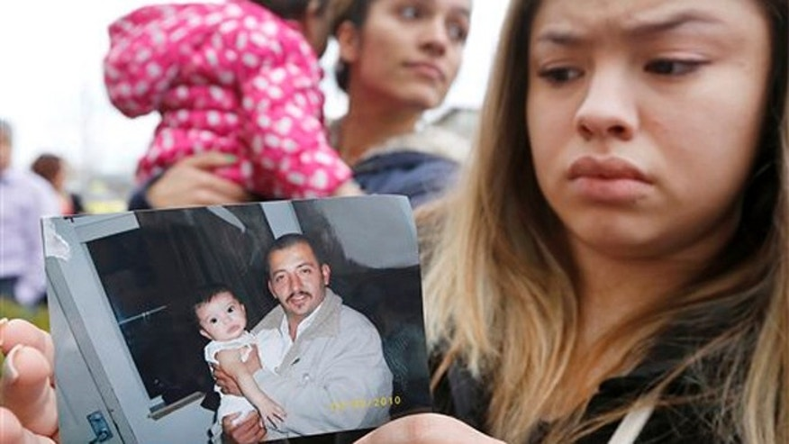 Erika Zambrano holds a 2010 photo of Antonio Zambrano-Montes, outside the city hall in Pasco, Wash.