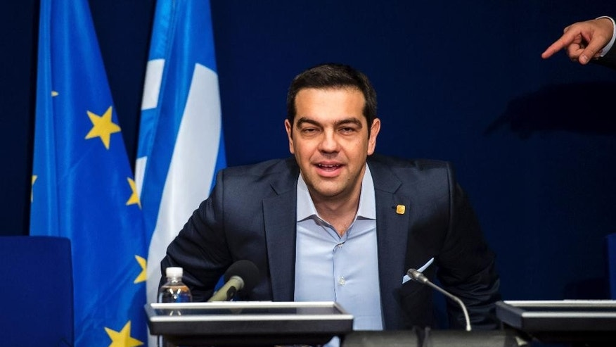 Greek Prime Minister Alexis Tsipras takes his seat during a media conference after an EU summit in Brussels on Thursday, Feb. 12, 2015. European Union leaders on Thursday said the full respect of the planned weekend cease-fire in eastern Ukraine will be essential before there could be a change in the sanctions regime imposed on Moscow. (AP Photo/Geert Vanden Wijngaert)