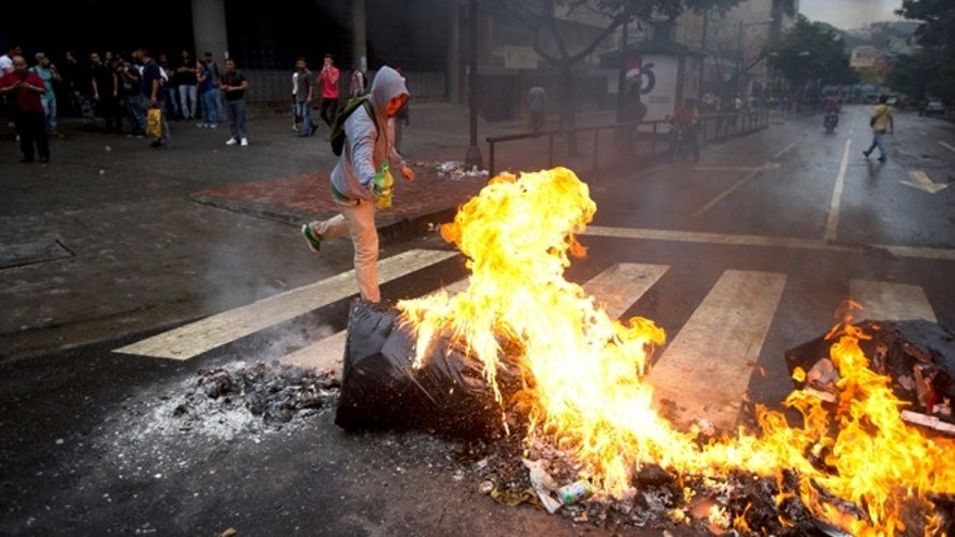 An opposition demonstrator sets a road block on fire in Caracas, Venezuela, Thursday, Feb. 12, 2015. Venezuelans staged dueling marches to mark the anniversary of last year's bloody protest movement that resulted in more than 40 people being killed, including both government supporters and opponents. Dozens of protesters remain jailed, while the social issues they railed against last year- a faltering economy, widespread shortages and pervasive violent crime - have only gotten worse. (AP Photo/Fernando Llano)