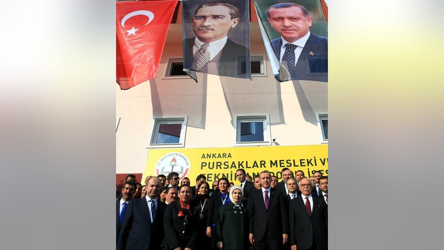 "FILE - In this Nov. 18, 2014 file photo, Turkish President Recep Tayyip Erdogan, center-right, and his wife Emine Erdogan pose for photos with officials in the courtyard of a Vocational School for Girls under a poster of Mustafa Kemal Ataturk, center, outside Ankara, Turkey. Turkey has long enshrined the secular ideals of founding father Mustafa Kemal Ataturk, particularly in an education system in which Islamic headscarves were until recently banned in schools and schoolchildren began the day reciting an oath of allegiance to Ataturk's legacy. Now proponents of Turkey's secular traditions claim President Recep Tayyip Erdogan is overturning those traditions by building a more Islam-focused education system to realize his stated goal of raising ""pious generations."" (AP Photo/File)"