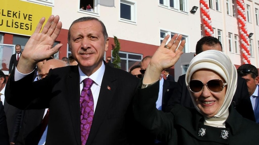 "FILE - In this Nov. 18, 2014 file photo, Turkish President Recep Tayyip Erdogan and his wife Emine Erdogan salute students of a Vocational School for Girls outside Ankara, Turkey. Turkey has long enshrined the secular ideals of founding father Mustafa Kemal Ataturk, particularly in an education system in which Islamic headscarves were until recently banned in schools and schoolchildren began the day reciting an oath of allegiance to Ataturk's legacy. Now proponents of Turkey's secular traditions claim President Recep Tayyip Erdogan is overturning those traditions by building a more Islam-focused education system to realize his stated goal of raising ""pious generations.""(AP Photo/File)"