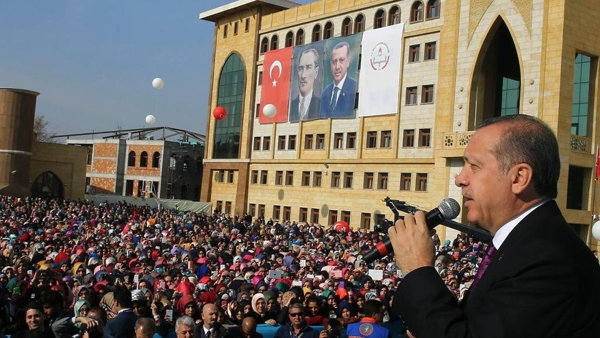 "FILE - In this Nov. 18, 2014 file photo, Turkish President Recep Tayyip Erdogan addresses students of a Vocational School for Girls outside Ankara, Turkey. Turkey has long enshrined the secular ideals of founding father Mustafa Kemal Ataturk, particularly in an education system in which Islamic headscarves were until recently banned in schools and schoolchildren began the day reciting an oath of allegiance to Ataturk's legacy. Now proponents of Turkey's secular traditions claim President Recep Tayyip Erdogan is overturning those traditions by building a more Islam-focused education system to realize his stated goal of raising ""pious generations."" (AP Photo/File)"