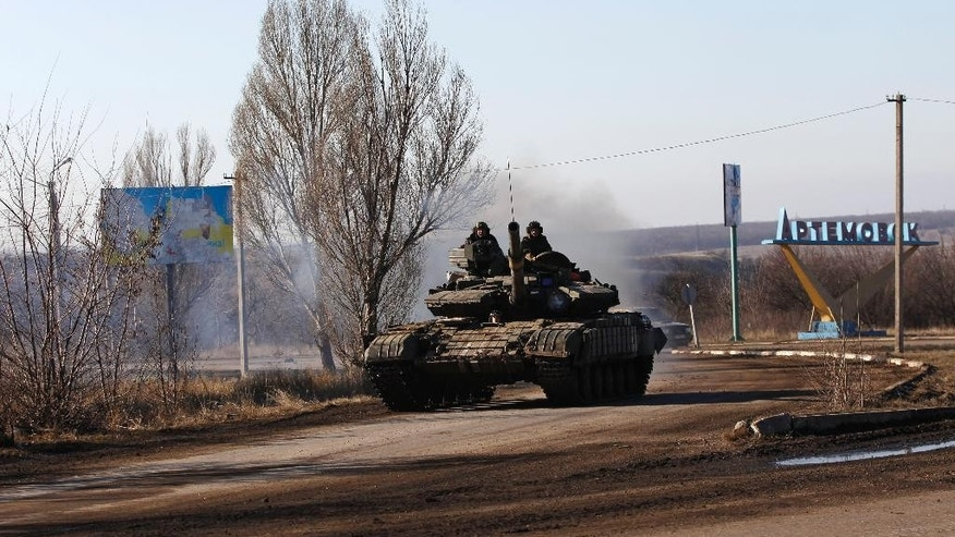 Ukrainian government troops ride a tank on a road towards Debaltseve near the town of Artemivsk, Ukraine, Friday, Feb. 13, 2015. The fighting between Russia-backed separatists and Ukrainian government forces has continued despite the agreement reached by leaders of Russia, Ukraine, Germany and France in the Belarusian capital of Minsk on Thursday. Much of the fighting had taken place near Debaltseve, a key transport hub that has been hotly contested in recent days. The leaders agreed to implement a cease-fire, set to take effect on Sunday, at one minute after midnight. (AP Photo/Petr David Josek)