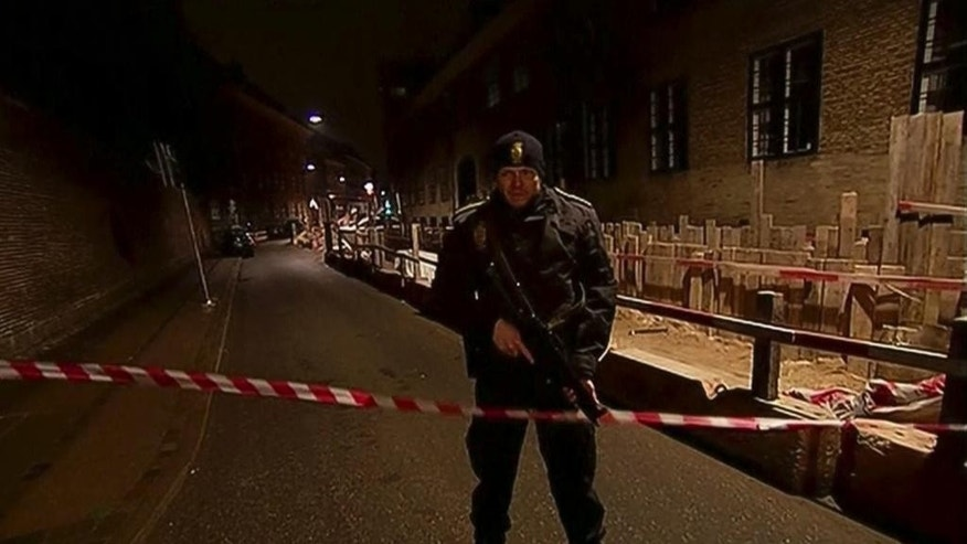 This image made from TV2 via Associated Press News video shows armed police guard behind police tape near a synagogue where police reported a shooting in downtown Copenhagen, Denmark, Sunday, Feb. 15, 2015.  One person was shot in the head and two police officers were shot in the arms and legs, police said. (AP Photo/TV2 via APTN) DENMARK OUT