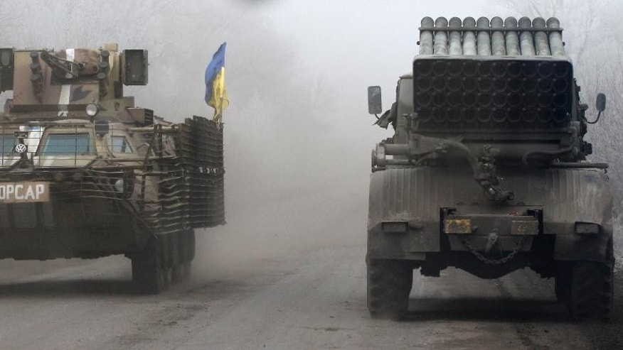 Ukrainian military vehicles travel on the road between the towns of Dabeltseve and Artemivsk, Ukraine, Saturday, Feb. 14, 2015. The fighting between Russia-backed separatists and Ukrainian government forces has continued despite the agreement reached by leaders of Russia, Ukraine, Germany and France in the Belarusian capital of Minsk on Thursday. Much of the fighting had taken place near Debaltseve, a key transport hub that has been hotly contested in recent days. The leaders agreed to implement a cease-fire, set to take effect on Sunday, at one minute after midnight. (AP Photo/Petr David Josek)