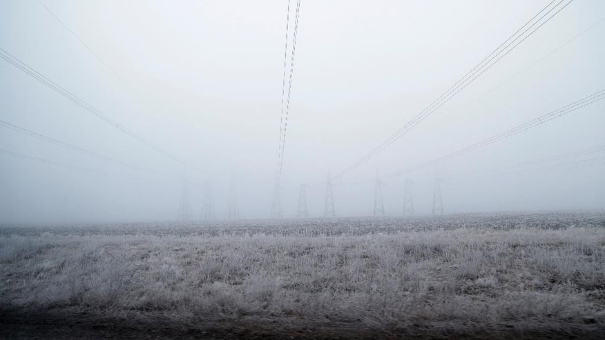 Electrical wires are seen near the road between the towns of Dabeltseve and Artemivsk, Ukraine, Saturday, Feb. 14, 2015. The fighting between Russia-backed separatists and Ukrainian government forces has continued despite the agreement reached by leaders of Russia, Ukraine, Germany and France in the Belarusian capital of Minsk on Thursday. Much of the fighting had taken place near Debaltseve, a key transport hub that has been hotly contested in recent days. The leaders agreed to implement a cease-fire, set to take effect on Sunday, at one minute after midnight. (AP Photo/Petr David Josek)