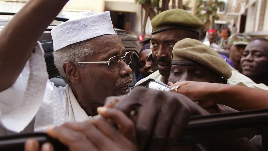 FILE - In this Friday, Nov. 25, 2005 file photo, former Chad dictator Hissene Habre, left, leaves a court in Dakar, Senegal. A former president of Chad accused of overseeing the deaths of thousands during his time in power will soon stand trial in Senegal on charges including war crimes and torture. The Extraordinary African Chambers, a special tribunal created to try ex-Chad dictator Hissene Habre, made the announcement Friday, Feb. 13, 2015 in response to the findings of a 19-month investigation into alleged crimes committed during his presidency. (AP Photo/Schalk van Zuydam, File)