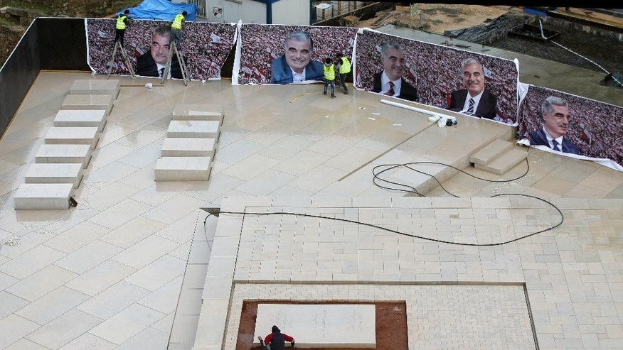 Workers set giant posters of slain former Lebanese Prime Minister Rafik Hariri in preparation to mark the 10th anniversary of his assassination, at his grave in downtown Beirut, Lebanon, Thursday, Feb. 12, 2015. The massive explosion that tore through his convoy on the Beirut seaside 10 years ago sent a tremor across the region and unleashed a popular uprising that briefly united the Lebanese and ejected Syrian troops from the country. But a decade later, and despite millions of dollars spent, justice remains elusive in a case that has been overshadowed by more recent turmoil. (AP Photo/Hussein Malla)