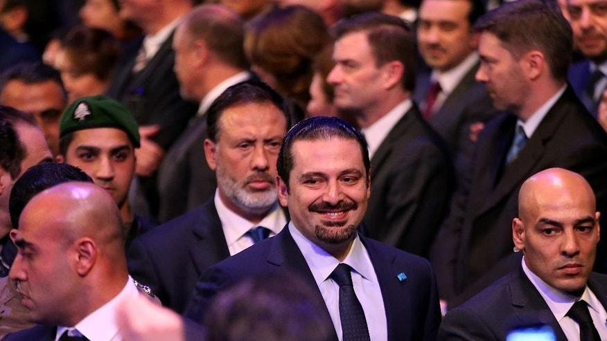 Former Lebanese Prime Minister Saad Hariri, center, escorted by his bodyguards, arrives to attend a ceremony to mark the tenth anniversary of the assassination of his father, former Prime Minister Rafik Hariri, in Beirut, Lebanon, Saturday, Feb. 14, 2015. Saad Hariri called on the militant Hezbollah group on Saturday to withdraw its forces from Syria saying their involvement in the civil war next door has backfired into Lebanon. (AP Photo/Hussein Malla)