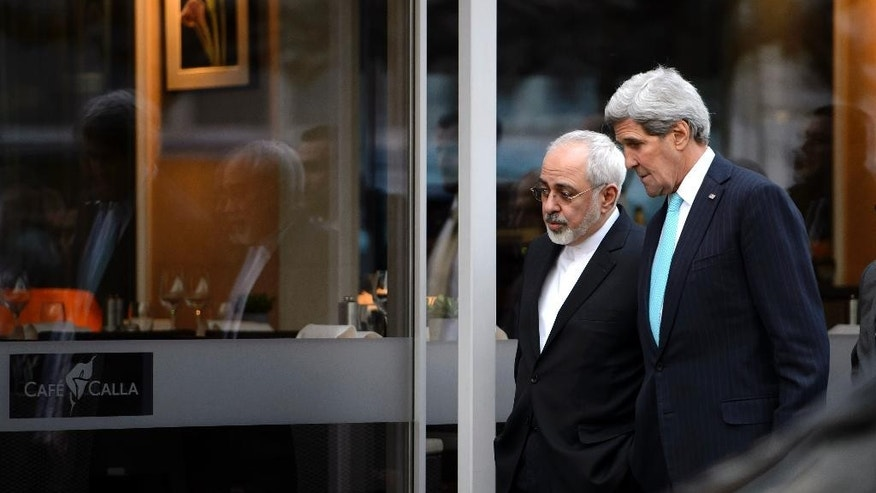 FILE - In this file photo taken Wednesday, Jan. 14, 2015, U.S. Secretary of State John Kerry, right, speaks with Iranian Foreign Minister Mohammad Javad Zarif as they walk in Geneva, Switzerland, ahead of the next round of nuclear discussion. Zarif has borne the brunt of the hard-liners' most recent criticism, particularly over a walk he took with Kerry during negotiations in Geneva in January 2015. (AP Photo/Keystone, Martial Trezzini, File)