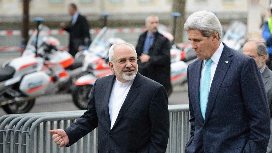 FILE - In this file photo taken Wednesday, Jan. 14, 2015, U.S. Secretary of State John Kerry, right, speaks with Iranian Foreign Minister Mohammad Javad Zarif, as they walk in Geneva, Switzerland, ahead of the next round of nuclear discussions. Zarif has borne the brunt of the hard-liners' most recent criticism, particularly over a walk he took with Kerry during negotiations in Geneva in January 2015. (AP Photo/Keystone, Laurent Gillieron, File)