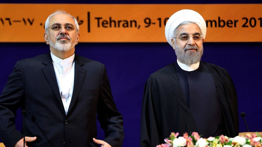 "Dec. 9, 2014:  Iranian President Hassan Rouhani, right, and Foreign Minister Mohammad Javad Zarif listen to the Iranian national anthem ahead of the ""World Against Violence and Extremism,"" conference."