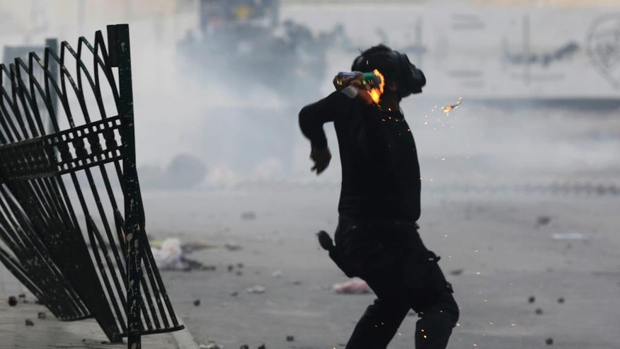 A Bahraini anti-government protester throws a petrol bomb toward an approaching armored police vehicle during clashes Friday, Feb. 13, 2015, in the Manama suburb of Bilad al-Qadeem, Bahrain. Protest marches were held and clashes erupted in opposition areas nationwide Friday, where many shops stayed closed as part of a three-day general strike called by the February 14 opposition youth group before Saturday's fourth anniversary of Bahrain's pro-democracy uprising. (AP Photo/Hasan Jamali)