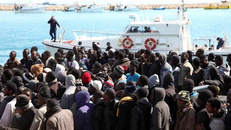 Migrants wait to disembark from a tug boat after being rescued in the Pozzallo harbor, Sicily, Italy, Sunday, Feb. 15, 2015. An Italian government official says four smugglers brandishing Kalashnikovs threatened an Italian Coast Guard motorboat that had just rescued migrants off the coast of Libya, where the security is rapidly deteriorating. Transport Minister Maurizio Lupi said the gunmen had sped to the scene Sunday afternoon aboard a small boat some 50 miles (80 kilometers) off Libyan shores. After threatening the Coast Guard rescuers who had taken aboard the migrants, three of the smugglers jumped aboard the then-empty migrants' boat to reclaim it and took off. In all, nearly 2,200 migrants were rescued in several operations Sunday, the Coast Guard said. They were being taken to Italian ports. (AP Photo/Francesco Malavolta)