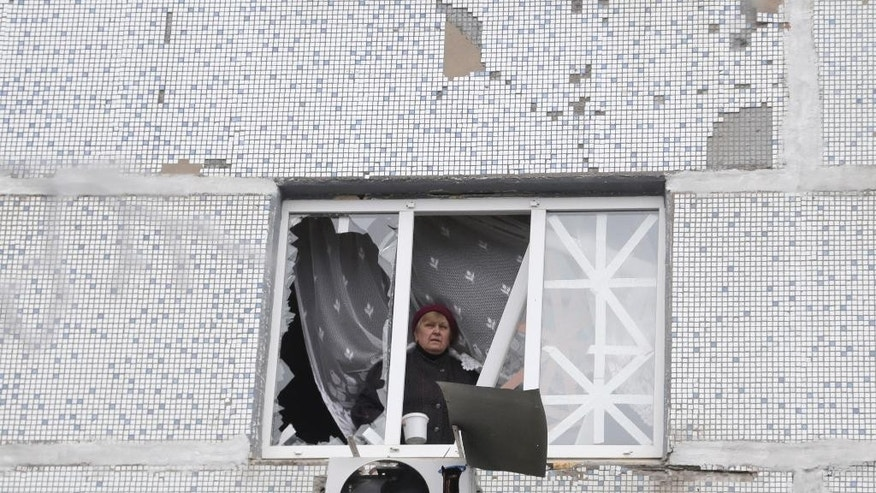 Woman looks out from a window of her apartment that was damaged in recent shelling between Russian-backed separatists and Ukrainian government forces in the town of Svitlodarsk, Ukraine, Sunday, Feb. 15, 2015. A cease-fire was declared in eastern Ukraine, kindling slender hopes of a reprieve from a conflict that has claimed more than 5,300 lives. (AP Photo/Petr David Josek)