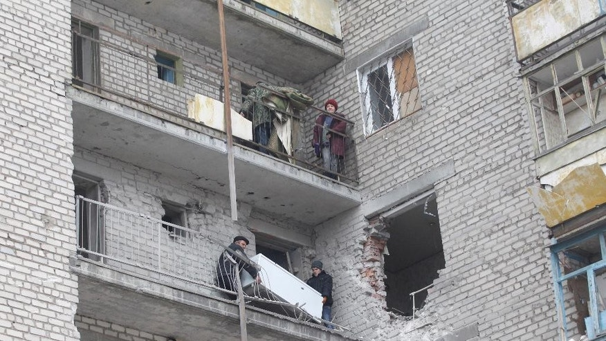 Residents carry a refrigerator through a balcony at an apartment building that was damaged in recent shelling between Russian-backed separatists and Ukrainian government forces in the town of Svitlodarsk, Ukraine, Sunday, Feb. 15, 2015. A cease-fire was declared in eastern Ukraine, kindling slender hopes of a reprieve from a conflict that has claimed more than 5,300 lives. (AP Photo/Petr David Josek)