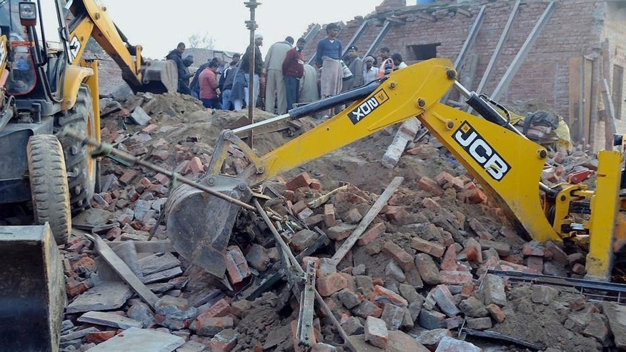 Rescuers use machinery to remove the debris after a building that was under construction collapsed overnight, in the town of Mughalsarai, about 300 kilometers (186 miles) southeast of Uttar Pradesh's state capital of Lucknow, India, Sunday, Feb. 15, 2015. The accident killed 13 members of a family of weavers who were sleeping on the ground floor, police said Sunday.(AP Photo/Press Trust of India)INDIA OUT
