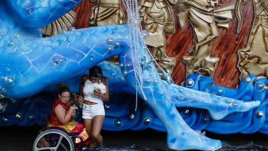 Revelers use a float as a windbreak before the start of Carnival celebrations at the Sambadrome in Rio de Janeiro, Brazil, Sunday, Feb. 15, 2015. (AP Photo/Leo Correa)