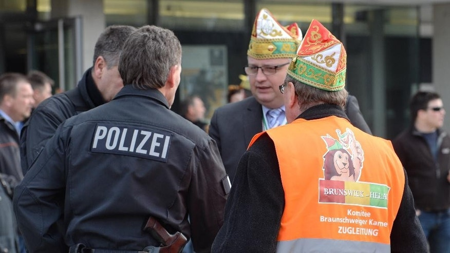 """Carnival parade organizers and police discuss in Braunschweig, Germany, Sunday, Feb. 15, 2015. Police in Braunschweig cancelled a popular carnival street parade because of fears of an imminent Islamist terror attack. Police spokesman Thomas Geese said police received credible information that there was a """"concrete threat of an attack"""" on Sunday's parade and therefore called on all visitors to stay at home. Braunschweig's carnival parade is the biggest one in northern Germany and draws around 250,000 visitors each year. (AP Photo/dpa, Julian Stratenschulte)"""