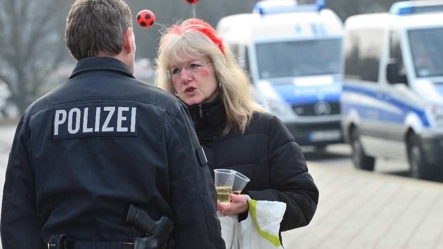 """A woman dressed up for carnival talks to a policeman in Braunschweig, Germany, Sunday, Feb. 15, 2015. Police in Braunschweig cancelled a popular carnival street parade because of fears of an imminent Islamist terror attack. Police spokesman Thomas Geese said police received credible information that there was a """"concrete threat of an attack"""" on Sunday's parade and therefore called on all visitors to stay at home. Braunschweig's carnival parade is the biggest one in northern Germany and draws around 250,000 visitors each year. (AP Photo/dpa, Julian Stratenschulte)"""