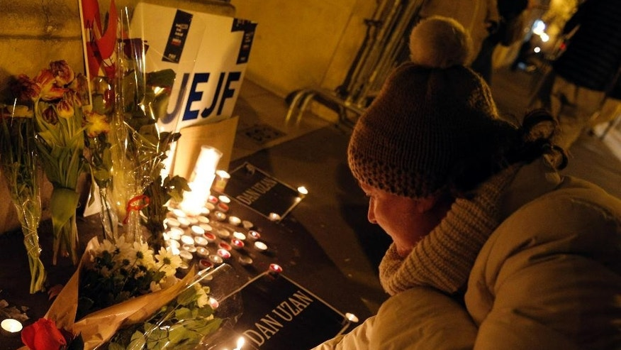 A woman lights a candle to pay respect to victims of the shooting attack in Copenhagen, at the Danish embassy in Paris, France, Sunday, Feb. 15, 2015. Danish police shot and killed a man early Sunday suspected of carrying out shooting attacks at a free speech event and then at a Copenhagen synagogue, killing two men, including a member of Denmark's Jewish community. Five police officers were also wounded in the attacks. The banner reading Dan Uzan, refers to the security guard killed. (AP Photo/Christophe Ena)