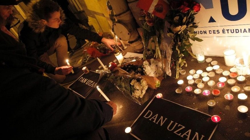 People light candles to pay respect to victims of the shooting attack in Copenhagen, at the Danish embassy in Paris, France, Sunday, Feb. 15, 2015. Danish police shot and killed a man early Sunday suspected of carrying out shooting attacks at a free speech event and then at a Copenhagen synagogue, killing two men, including a member of Denmark's Jewish community. Five police officers were also wounded in the attacks. The banner reading Dan Uzan, refers to the security guard killed. (AP Photo/Christophe Ena)