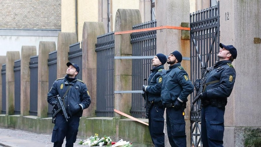 Danish police officers stand outside of a synagogue, Sunday, Feb. 15, 2015, where a gunman opened fire in Copenhagen, Denmark.  Danish police shot and killed a man early Sunday suspected of carrying out shooting attacks at a free speech event and then at a Copenhagen synagogue, killing two men, including a member of Denmark's Jewish community. Five police officers were also wounded in the attacks. (AP Photo/Michael Probst)