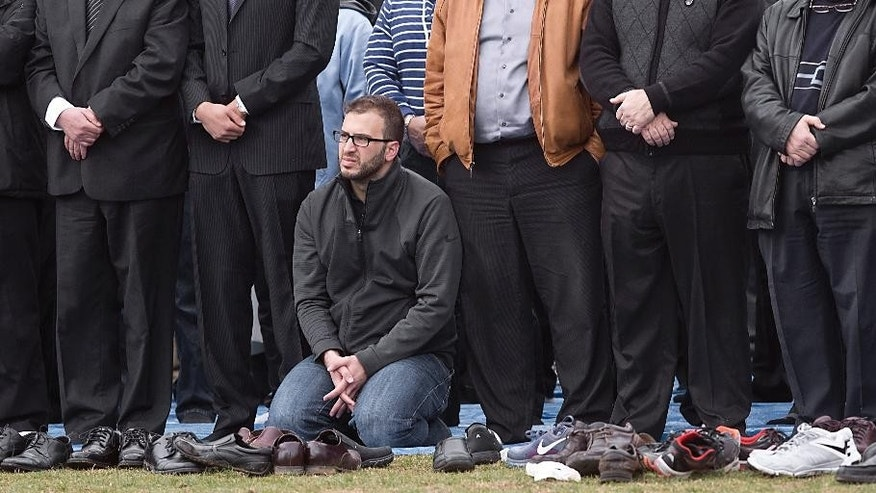 Farris Barakat, center, remains on his knees after prayer during a funeral service for his brother Deah Shaddy Barakat, Thursday, Feb. 12, 2015, in Raleigh, N.C. Deah Shaddy Barakat, his wife Yusor Mohammad Abu-Salha, and her sister Razan Mohammad Abu-Salha were killed Tuesday at a condominium in Chapel Hill, N.C. Craig Stephen Hicks was charged with three counts of first-degree murder. (AP Photo/The News & Observer, Corey Lowenstein)