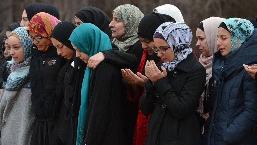 Women mourn near the graves of Deah Shaddy Barakat, Yusor Mohammad Abu-Salha and Razan Mohammad Abu-Salh, Thursday, Feb. 12, 2015, in Wendell, N.C. Craig Stephen Hicks was charged with three counts of first-degree murder for their deaths near the University of North Carolina-Chapel Hill campus Tuesday. (AP Photo/The News & Observer, Chuck Liddy)