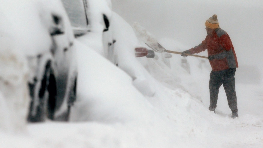 A man shovels snow in the East Boston neighborhood of Boston, Sunday, Feb. 15, 2015. A storm brought a new round of wind-whipped snow to New England on Sunday, threatening white-out conditions in coastal areas and forcing people to contend with a fourth winter onslaught in less than a month. (AP Photo/Michael Dwyer)