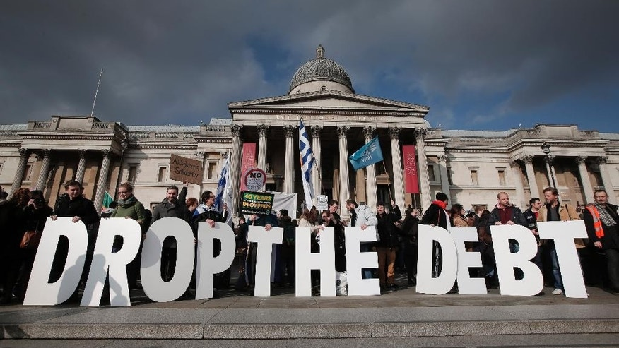 "Backdropped by Britain's National Gallery in central London, protesters hold placards during a rally to show solidarity with Greece, Sunday, Feb. 15, 2015.  Hundreds of protesters gathered in support of the new government and the anti-austerity movement in Greece. Greece's new left-wing government is pressing for a short-term ""bridge"" agreement with eurozone lenders and a longer-term debt relief deal later this year. (AP Photo/Lefteris Pitarakis)"