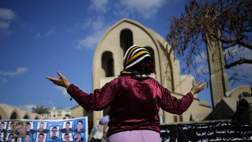 In this Friday, Feb. 13, 2015 photo, a Coptic Christian woman prays for the release of 21 Coptic Egyptian men whose were abducted by Islamic State militants in the central city of Sirte, Libya more than a month ago, during a protest at the Coptic cathedral in Cairo, Egypt. A video purporting to show the mass beheading of Coptic Christian hostages was released Sunday, Feb. 15, 2015, by militants in Libya affiliated with the Islamic State group. (AP Photo/Hassan Ammar)