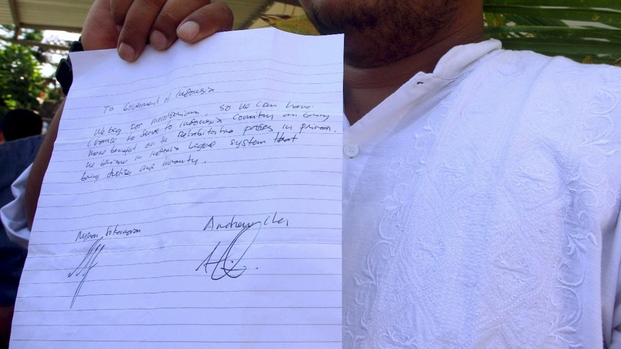 Thursday, Feb. 5, 2015: Indonesian human rights activist, Matius Arif  Mirdjadja holds a letter from death-row prisoners Myuran Sukumaran and Andrew Chan that asks the Indonesian government to spare their lives, in front of Denpasar's prison in Bali, Indonesia.
